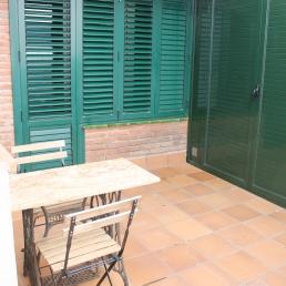 zona de terraza con mesa y sillas. Tiene un armario de aluminio con ventilación.