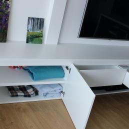 detalle interior mueble lacado con estante interior y cajones debajo de la tv colgada a pared.