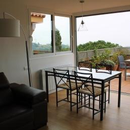 rincón de mesa comedor con lámpara de cristal para que quede integrada con el paisaje exterior.