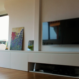 mueble comedor con tv colgada a pared. Debajo hay dos cajones y un lugar para los aparatos electrónicos.
