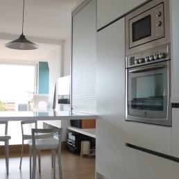 columna forn i microones amb la despensa al costat i taula volada amb armari persiana.