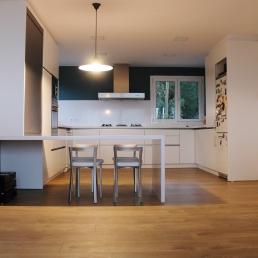 Tot acabat. Paviment de parquet, mobles lacats blancs i silestone blanc. El toc pintat a la paret de la campana, per trencar el blanc de la cuina.