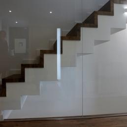 Escala de parquet conjunt resta paviment del primer pis amb un tancament de seguretat de vidre per evitar caigudes. El vidre dona profunditat i llum, tant a les escales que baixen com a les escales que pugen.