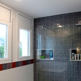 detall sanefa combinat de colors trencant el blanc paret i blanc alumini finestres. S'han fet uns perstatges dins la dutxa folrats amb silestone blanc.