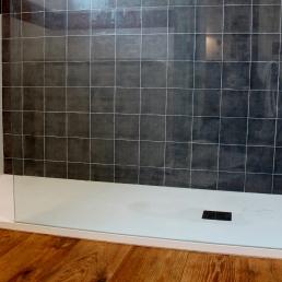 Plat de dutxa extra pla amb mampara de vidre transparent.