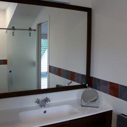 Aqui es veu el moble del bany i a traves del mirall la mampara de vidre a l'àcid tancament wc.