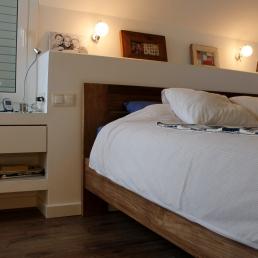 Capçal del llit donant continuitat al moble sota finestra, tot d'obra i amb dos calaixos de dm penjats.