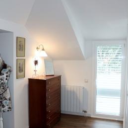 Racó de l'habitació amb calaixera i una llum, al fons una porta que dona a l'exterior.