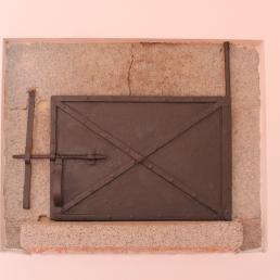 Imatge del forn tancat amb la portella original de la masia.