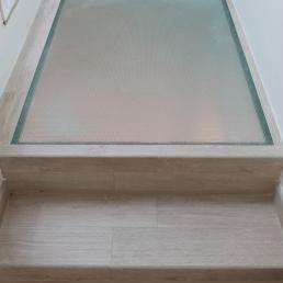 Escala combinat amb el parquet, en el petit replà hem col.locat un vidre armat per donar llum al pis inferior. Despres es continua escala amb rajola recuperada de la masia.